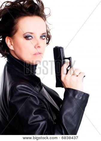 Woman In Leather Wear Holding Gun Over White Background