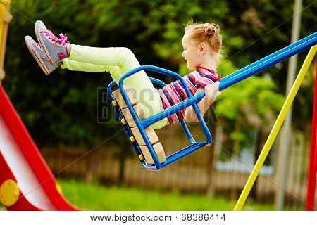 Happy little girl swinging on playground area