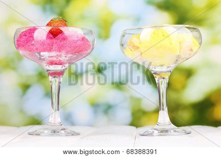 delicious ice cream on wooden table on bright background