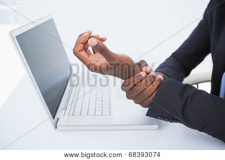 Businessman holding his sore wrist from typing in his office