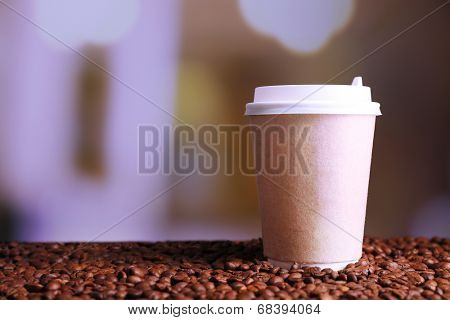Cup of strong coffee on coffee beans, on bright background