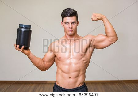 Portrait of a muscular man posing with nutritional supplement in gym