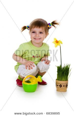 Cute Little Girl Watering Yellow Flower. Studio Shot