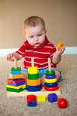 foto of playgroup  - Baby boy playing with stacking learning toy - JPG