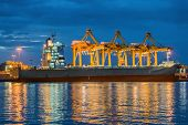 image of shipyard  - Container Cargo freight ship with working crane bridge in shipyard at dusk
