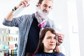 stock photo of hairspray  - Male coiffeur giving women hairstyling with hairspray in shop - JPG