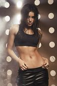 pic of smoking woman  - Sexy sporty woman with slim stomach over background with holes and smoke - JPG