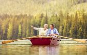 stock photo of paddling  - Senior couple paddling on boat with mountains in background - JPG