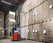 foto of lift truck  - Reach truck forklift lifting a pallet from the top shelf in a large warehouse - JPG