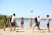 stock photo of volleyball  - Group of friends playing volleyball at beach - JPG