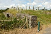 foto of old stone fence  - An old stone bridge overgrown with grass with a rickety wooden fence - JPG