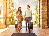 stock photo of lounge room  - Young couple standing at hotel corridor upon arrival looking for room holding suitcases - JPG