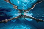 foto of breast-stroke  - Fit swimmer training by himself in the swimming pool at the leisure centre - JPG