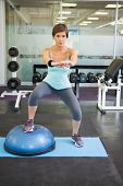 pic of squatting  - Fit brunette using bosu ball for squats at the gym - JPG