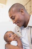foto of babygro  - Happy father spending time with baby on the couch at home in the living room - JPG