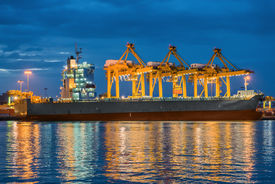 stock photo of shipyard  - Container Cargo freight ship with working crane bridge in shipyard at dusk  - JPG