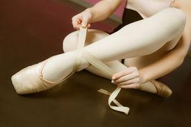 stock photo of ballerina  - Ballerina tying the ribbon on her ballet slippers in the ballet studio - JPG