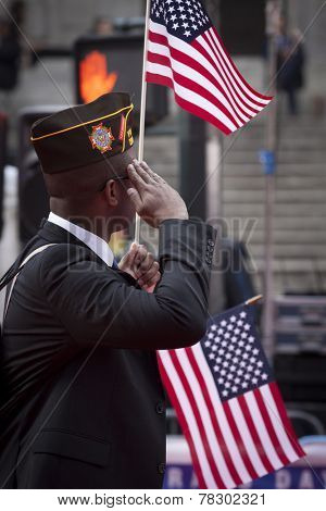 NEW YORK - NOV 11, 2014: A vet carrying an American Flag salutes as he marches past the VIP stage during the 2014 America's Parade held on Veterans Day in New York City on November 11, 2014.