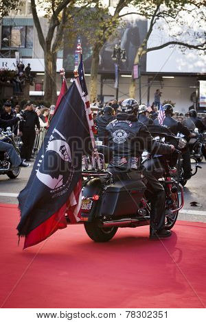 NEW YORK - NOV 11, 2014: A US vet rides a Harley Davidson motorcycle with the American, USMC, and POW / MIA Flags attached to the back during the 2014 America's Parade on Veterans Day on Nov 11, 2014.
