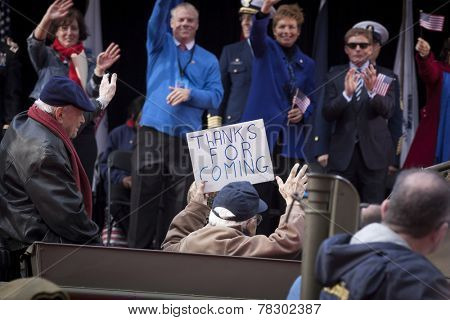 NEW YORK - NOV 11, 2014: An elderly vet waves to the people on the VIP stage while holding a sign that says Thanks For Coming during the 2014 America's Parade on Veterans Day on November 11, 2014.