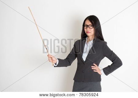 Asian female teacher angry and holding a stick, standing on plain background.
