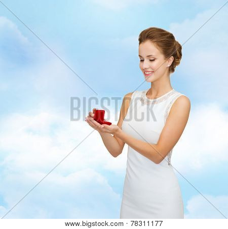 wedding, love, engagement and people concept - smiling woman in white dress holding red gift box with diamond ring over blue cloudy sky background
