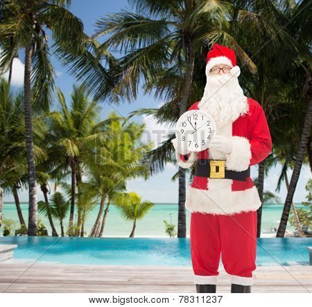 christmas, holidays, travel and people concept - man in costume of santa claus with clock showing twelve over tropical beach and swimming pool background