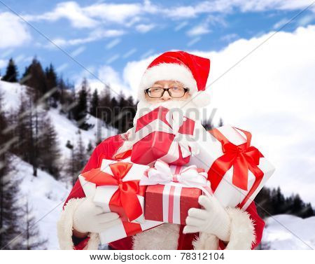 christmas, holidays and people concept - man in costume of santa claus with gift boxes over snowy mountains background