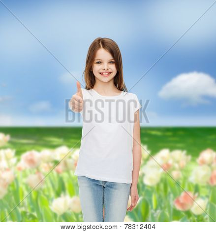 advertising, childhood, nature, gesture and people concept - smiling girl in white t-shirt showing thumbs up over flower field background