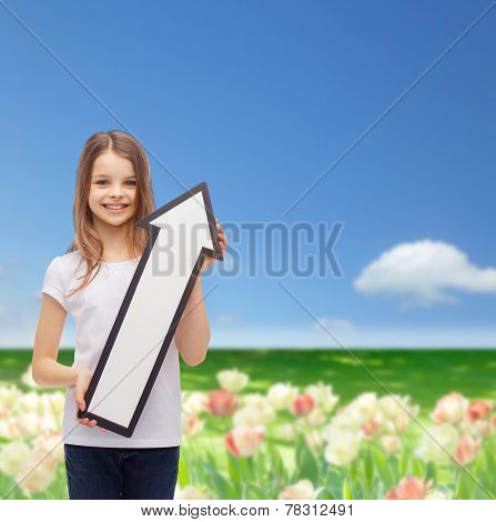 advertising, direction, nature, gardening and childhood concept - smiling girl with white arrow pointing up over flower field background