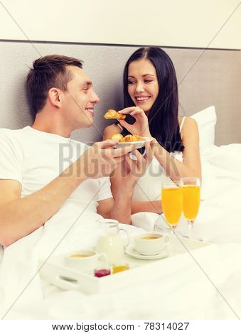 hotel, travel, relationships and happiness concept - smiling couple having breakfast in bed in hotel room