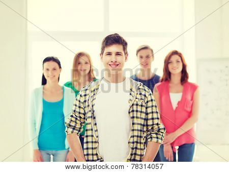 friendship and education concept - smiling male student in front of group of classmates
