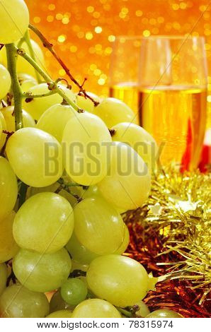 a bunch of the spanish grapes of luck and glasses with champagne, with a festive golden background