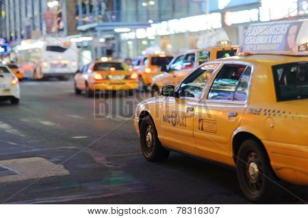 NEW YORK - SEPTEMBER 28: yellow cabs at area near Times Square at night on September 28, 2011 in New-York, USA. Times Square is a major commercial intersection and a neighborhood in Midtown Manhattan