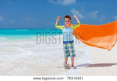 Cute little boy having fun on tropical beach during summer vacation