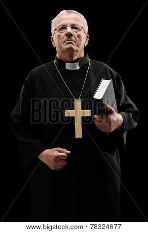 Mature male priest holding a holy bible on black background