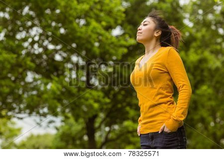 Low angle view of beautiful young woman with eyes closed in park