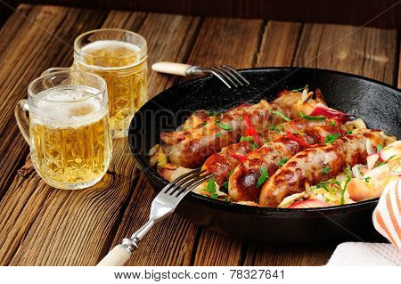Sausages Fried In Cast Iron Skillet With Two Beer Mugs