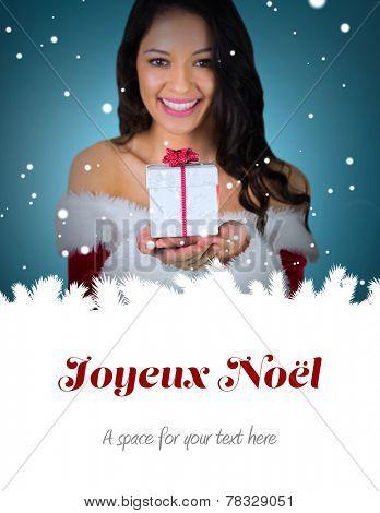 pretty girl in santa outfit holding gift against joyeux noel