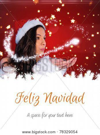 pretty girl in santa outfit blowing against feliz navidad