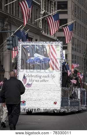 NEW YORK - NOV 11, 2014: Vets wave American Flags from the Dignity Memorial parade vehicle platform during the 2014 America's Parade held on Veterans Day in New York City on November 11, 2014.
