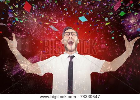 Geeky young businessman with arms out against colourful fireworks exploding on black background