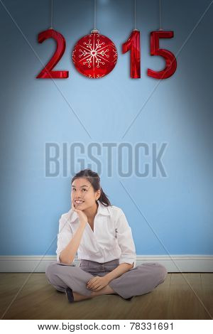 Businesswoman sitting cross legged thinking against blue room with wooden floor