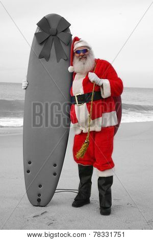 Colorized Santa Claus holds his surfboard while on the beach with the ocean blue behind him. Santa Loves Sports the beach and the outdoors. Santa loves to surf on his surfboard as much as he can