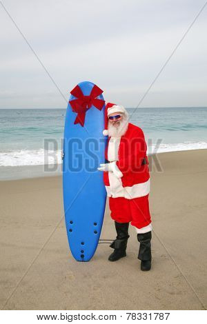 Santa Claus stands on the beach by the Ocean holding a Blue Surfboard with a Large Red Bow on it as a Christmas Gift to some lucky Boy or Girl. Santa Claus is one cool cat and love to give things out