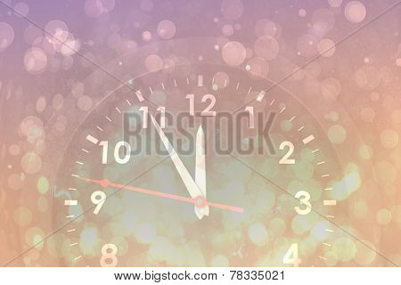 Clock counting down to midnight against pink abstract light spot design