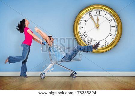 Young couple having fun with shopping cart against blue room with wooden floor