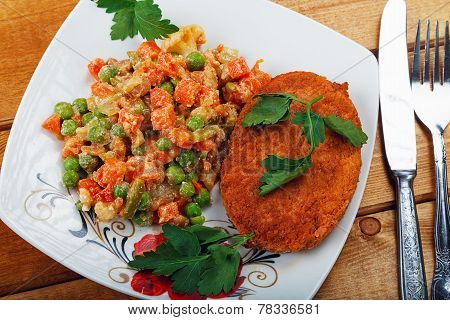Fish Cutlet With A Vegetable Garnish On A Table