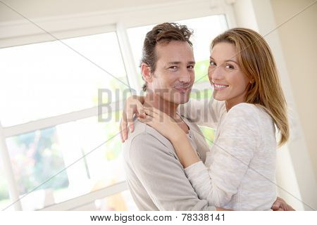 Smiling mature couple embracing each other at home