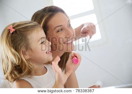 Mother and daughter in bathroom brushing her teeth